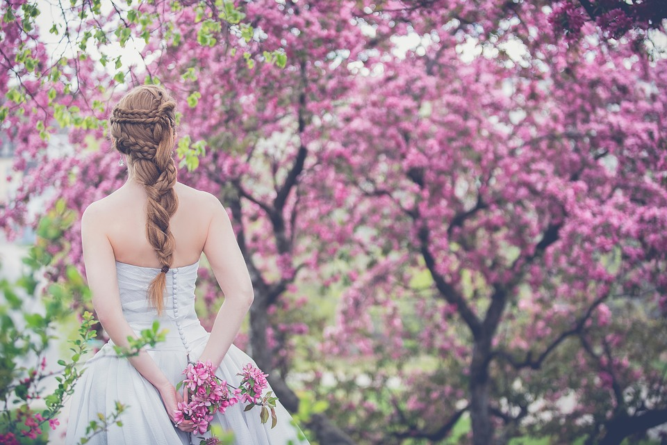 woman in wedding gown while having fishtail braid hairstyle