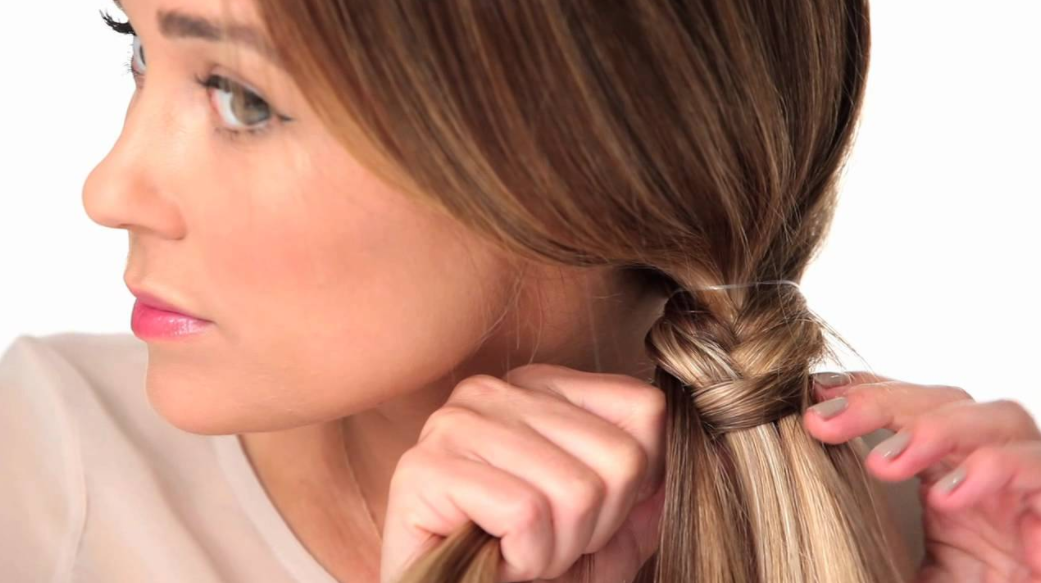 Woman fishtail braiding her hair