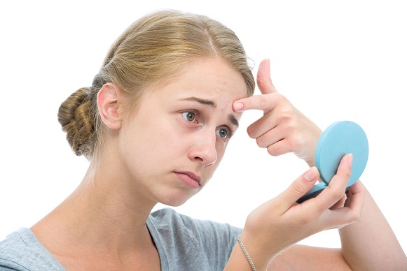 Blonde woman looking at a compact mirror to get rid of her pimples