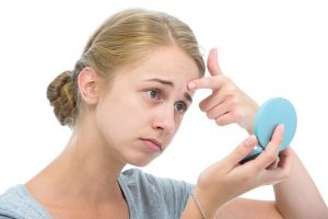 Woman looking at a handheld mirror and planning to get rid of her pimples