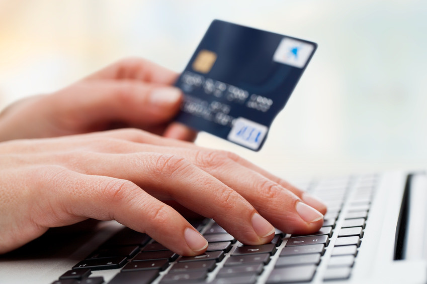person typing on the keyboard while holding credit card on the left hand