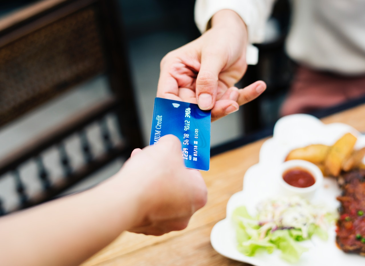 Two person holding a blue credit card