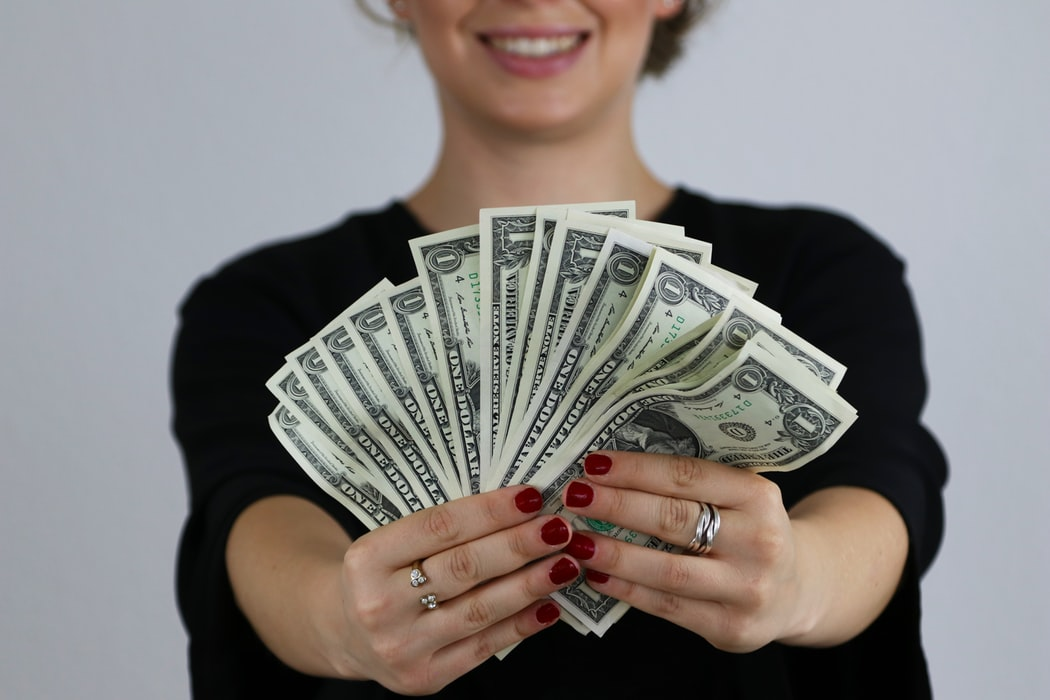 selective focus photography of woman holding US dollar banknotes